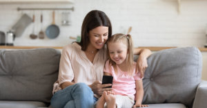 A woman in child looking at a device to stay in touch with family